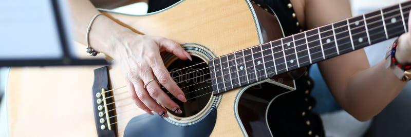 Mains femelles tenant la guitare acoustique occidentale se reposant sur le divan ? la maison photos libres de droits