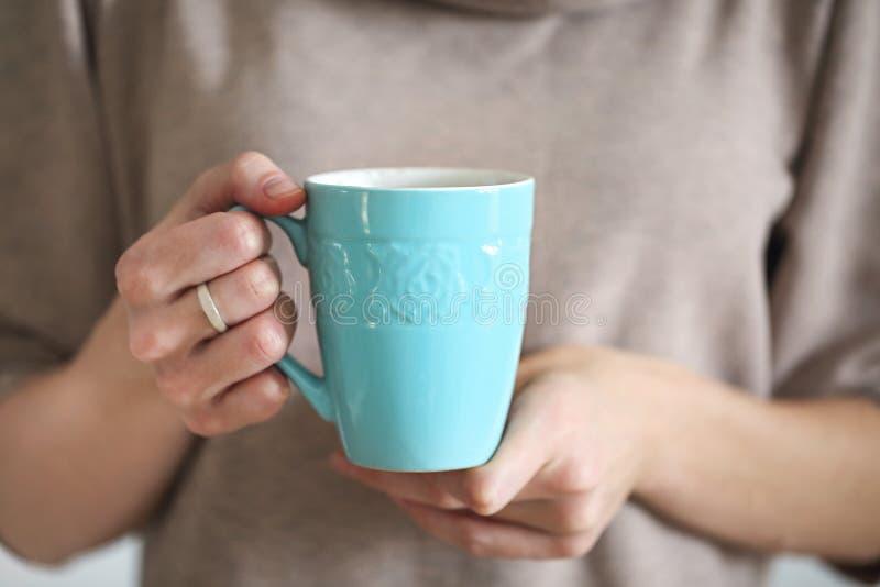 Mains femelles tenant la tasse de la boisson nouvellement fabriquée de cacao images stock