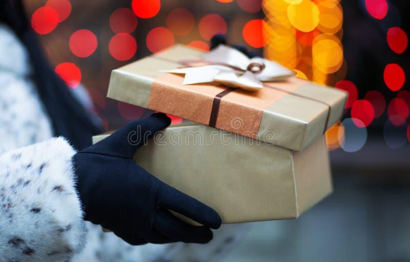 Mains femelles tenant le boîte-cadeau avec un arc au backg de bokeh de tache floue images stock