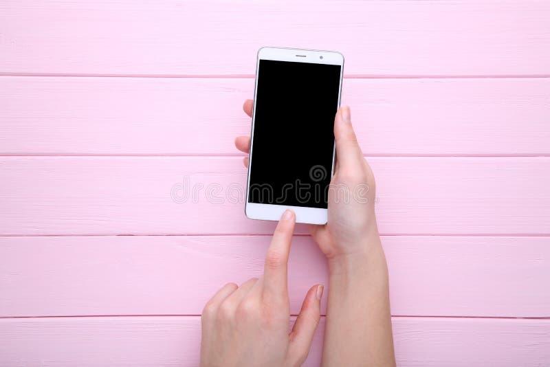 Mains femelles tenant le téléphone portable avec l'écran vide sur le fond en bois rose Smartphone sur le Tableau en bois photos stock