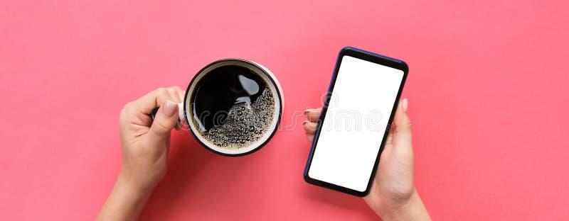 Mains femelles tenant le téléphone portable noir avec l'écran et la tasse blancs vides de café Image de maquette avec l'espace de image stock
