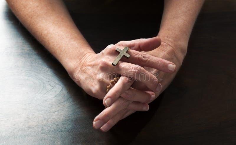 Mains femelles tenant une croix religieuse priant pour la paix photographie stock