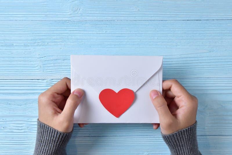 Mains femelles tenant une lettre d'amour photos stock