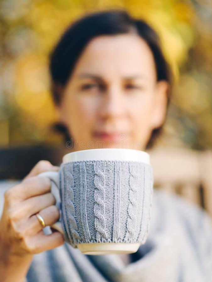 Mains femelles tenant une tasse de café chaud de thé dans le paysage d'automne - photos stock