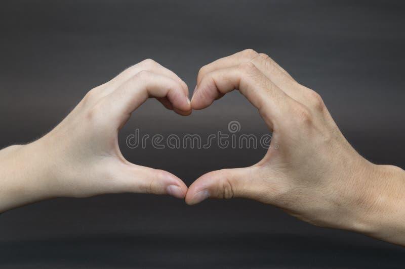 Mains form?es au coeur sur le fond noir photo libre de droits