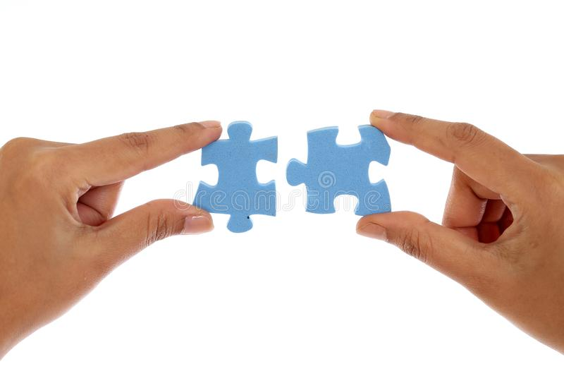 Mains fusionnant deux morceaux de puzzle denteux contre le blanc photos stock