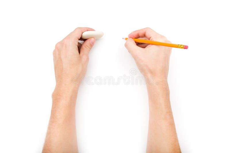 Mains humaines avec le crayon et la gomme image stock