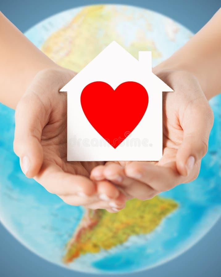 Mains humaines tenant la maison de papier avec le coeur rouge photographie stock