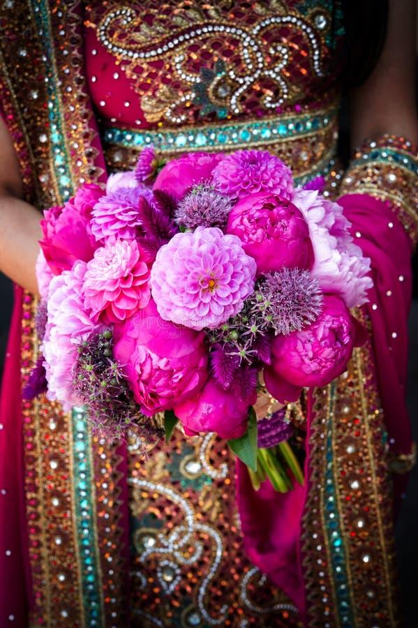 Mains indiennes de mariées retenant le bouquet