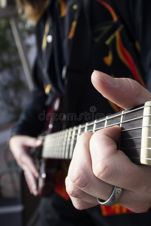 Mains jouant la guitare images stock