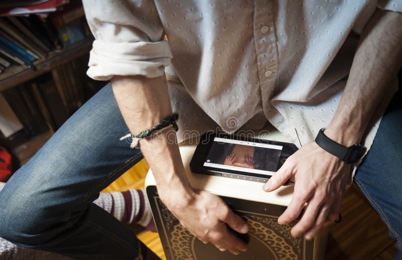 Mains jouant la percussion avec une boîte de flamenco et un smartphone photos stock