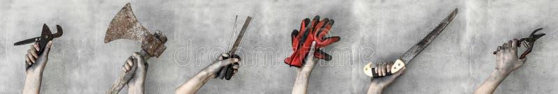 Mains jugeant des outils de travail d'isolement sur le fond gris image libre de droits