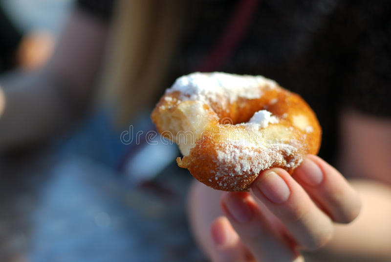 Mains jugeant le beignet bited épousseté avec la fin en poudre de sucre  photo stock