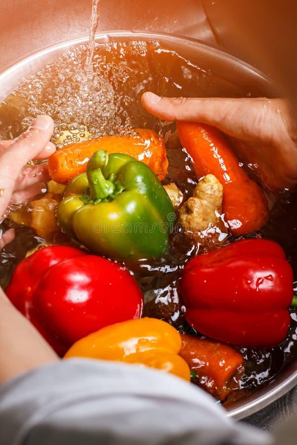 Mains lavant des légumes dans l'eau photo libre de droits