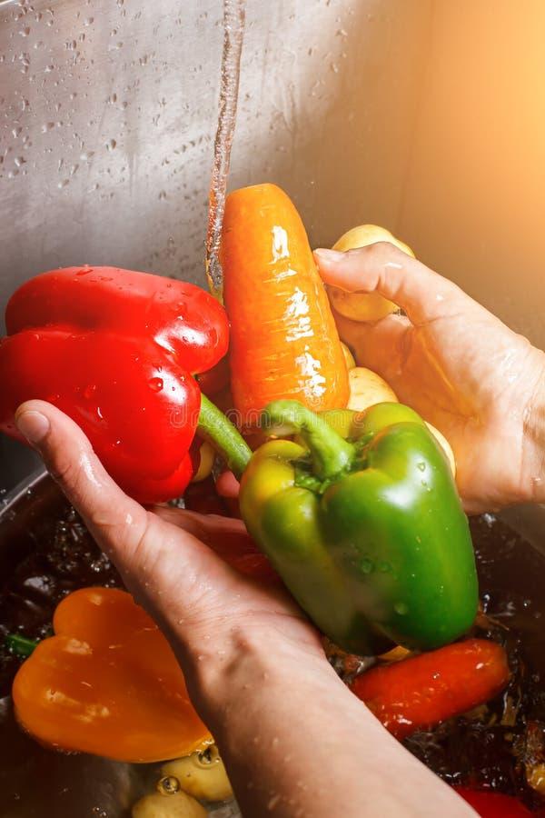 Mains lavant la carotte et le paprika images libres de droits