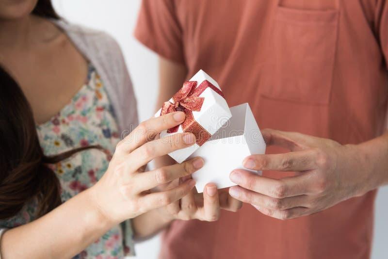 Mains mâles et femelles avec la boîte-cadeau photos libres de droits