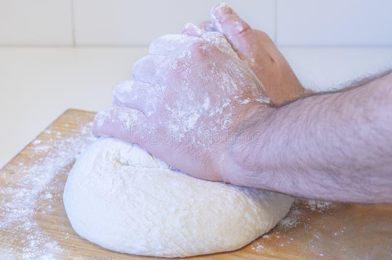 Mains malaxant la pâte de pain de blé photos stock