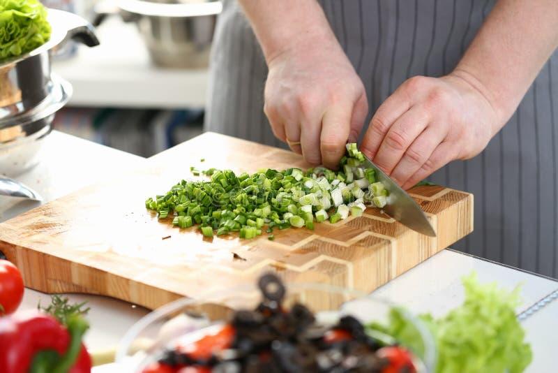 Mains masculines coupant l'ingrédient d'oignon blanc de salade photographie stock libre de droits