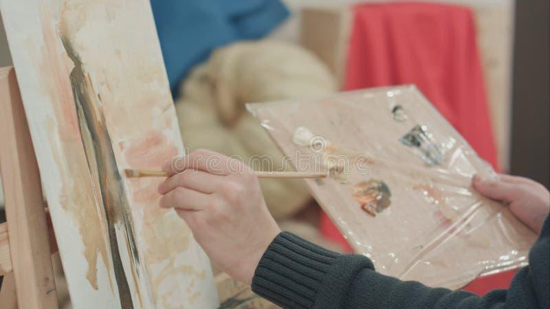 Mains masculines d'artiste appliquant des courses de brosse sur la toile et tenant la palette image libre de droits