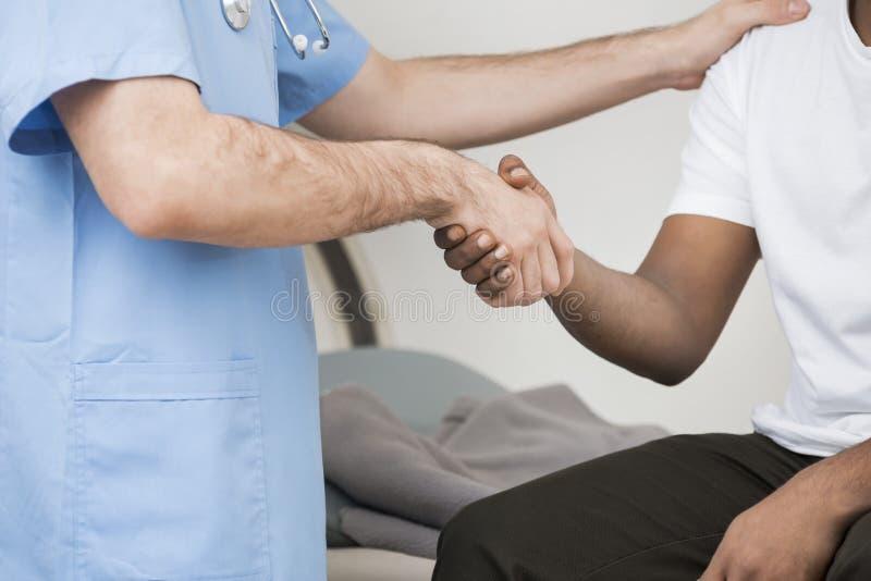 Mains masculines d'And Patient Shaking de radiologue après balayage de CT images libres de droits