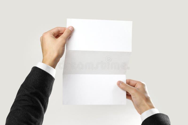 Mains masculines dans la chemise blanche et la veste noire tenant une feuille de livret blanc de papier triple D'isolement sur le image libre de droits