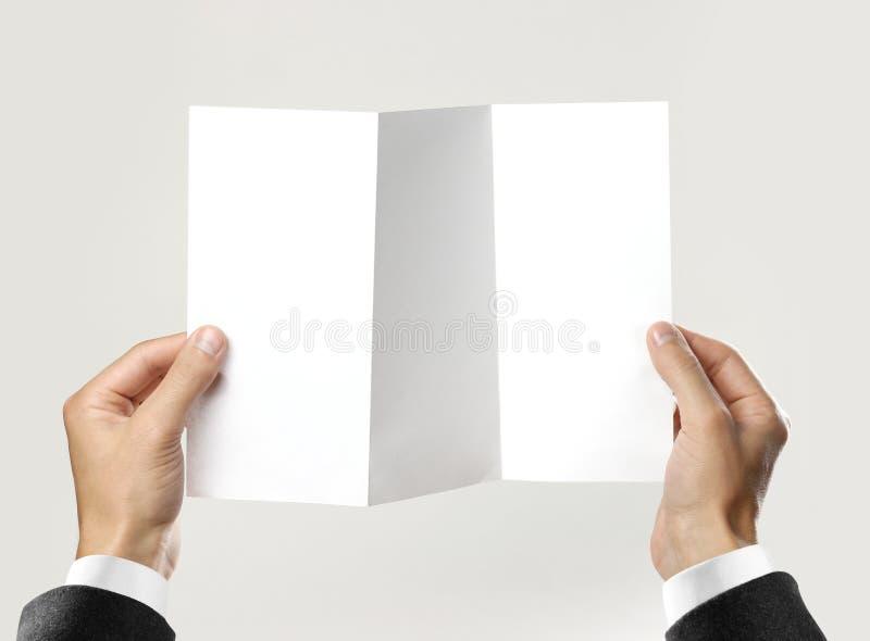 Mains masculines dans la chemise blanche et la veste noire tenant une feuille de livret blanc de papier triple D'isolement sur le images stock