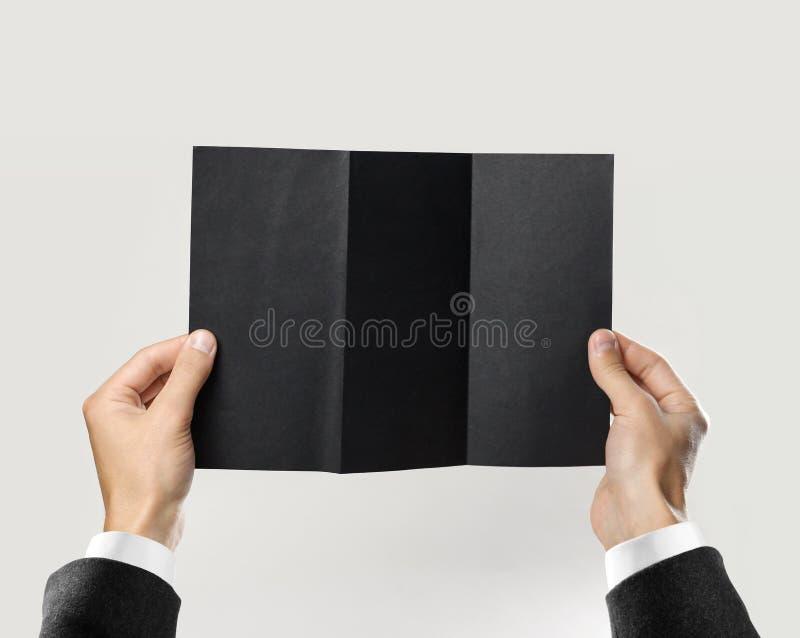 Mains masculines dans la chemise blanche et la veste noire tenant une feuille de livret noir de papier triple D'isolement sur le  photographie stock libre de droits