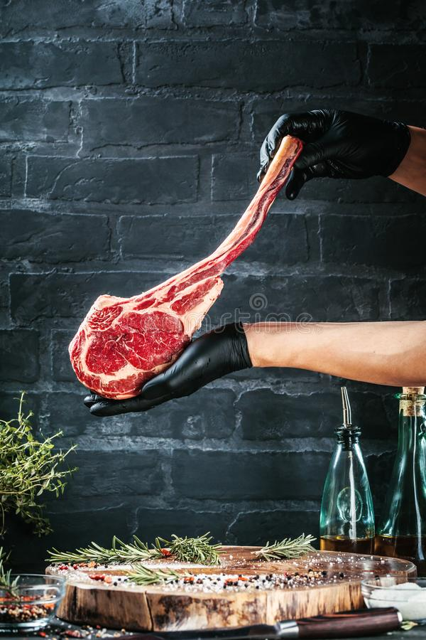 Mains masculines de bifteck de boeuf de tomahawk de participation de boucher ou de cuisinier sur le fond rustique foncé de table  photos stock