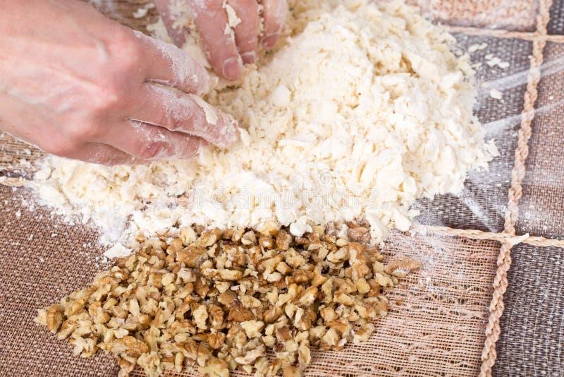 Mains masculines faisant la pâte avec des noix image stock