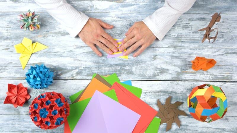 Mains masculines pliant le jouet d'origami photographie stock libre de droits