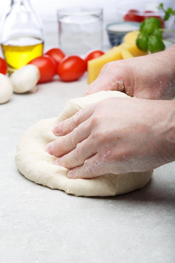 Mains masculines pr?parant la p?te pour la pizza photo stock
