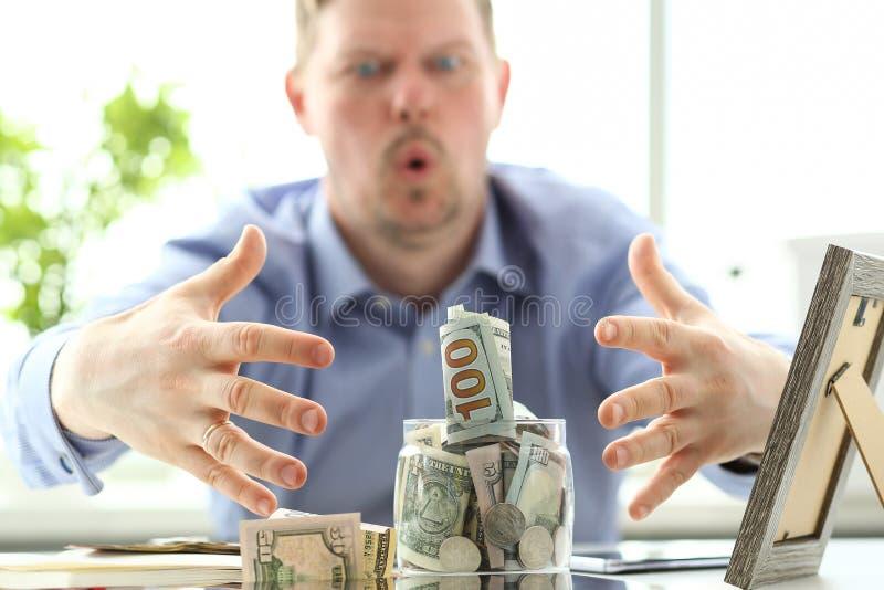 Mains masculines saisissant le grand gros pot complètement de devise des USA comme geste d'avidité photos stock