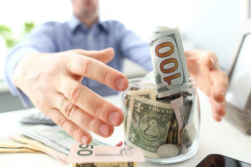 Mains masculines saisissant le grand gros pot compl?tement de devise des USA comme geste d'avidit? image libre de droits