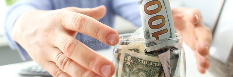 Mains masculines saisissant le grand gros pot compl?tement de devise des USA comme geste d'avidit? photo libre de droits