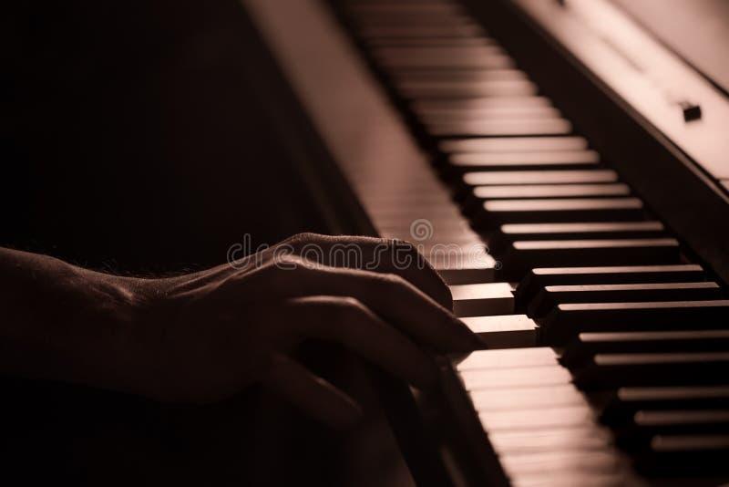 Mains masculines sur le plan rapproché de clés de piano d'un beau fond coloré images libres de droits