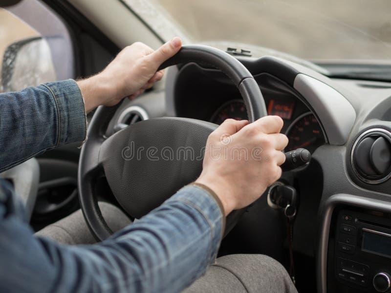 Mains masculines sur le volant, à l'intérieur de la cabine, fin  Homme conduisant un v?hicule images stock