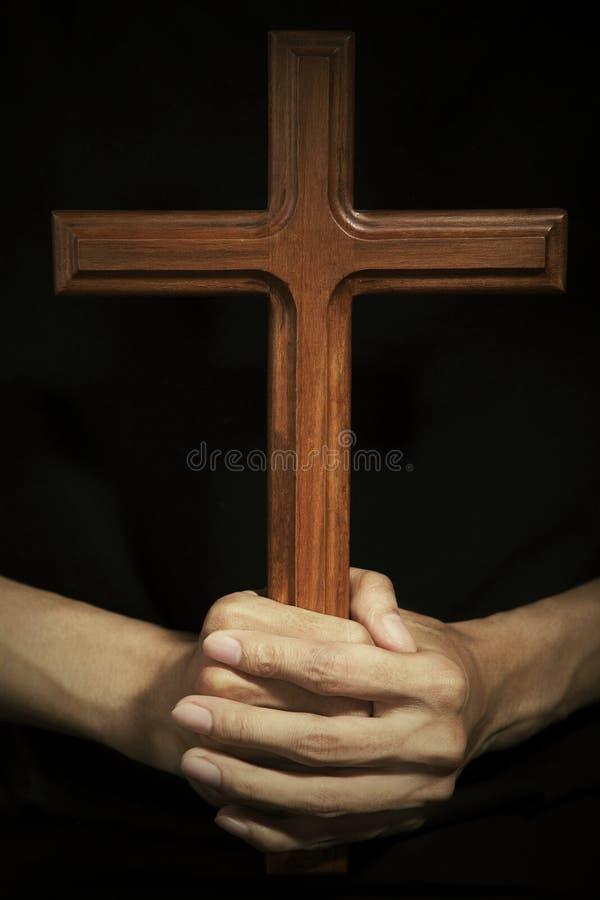 Mains masculines tenant la croix en bois images libres de droits