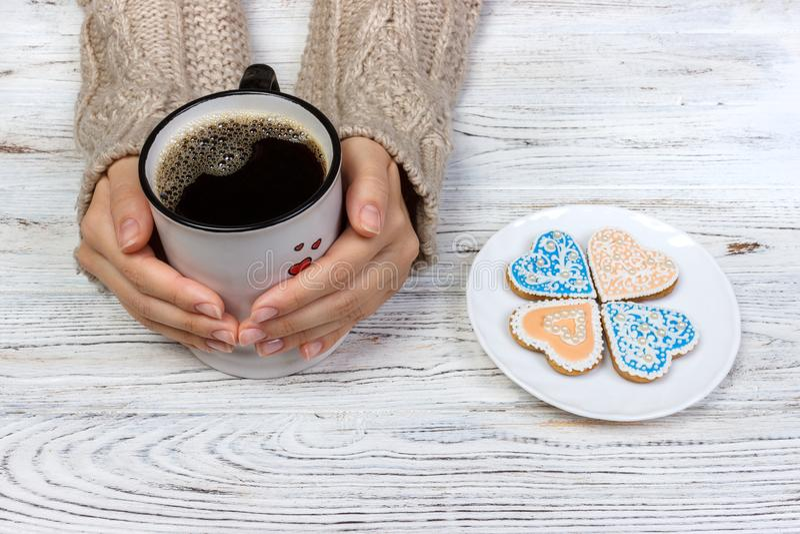 Mains masculines tenant le biscuit dans les formes de coeur et une tasse de café tonalité Foyer sélectif photo stock