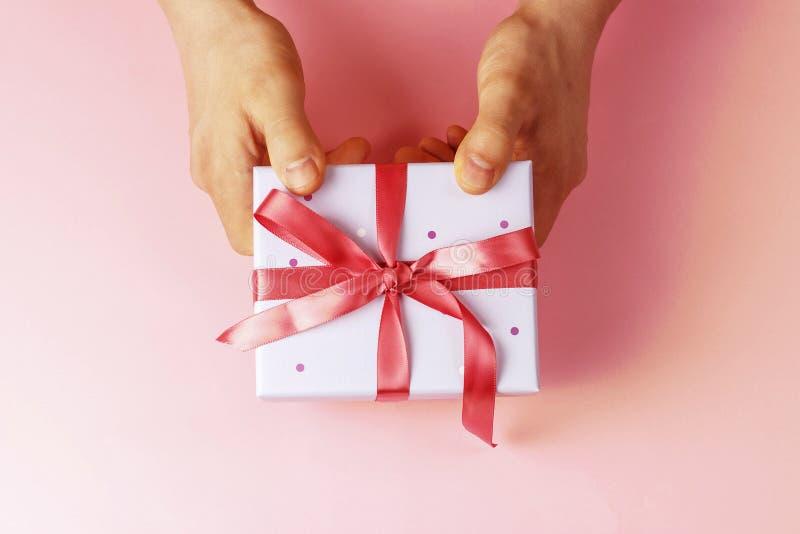 Mains masculines tenant le boîte-cadeau avec le ruban sur le fond rose, vue supérieure photo stock