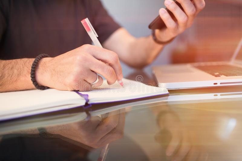Mains masculines tenant le smartphone et faisant des notes dans le bloc-notes pendant le temps de travail au bureau Fond brouillé image stock