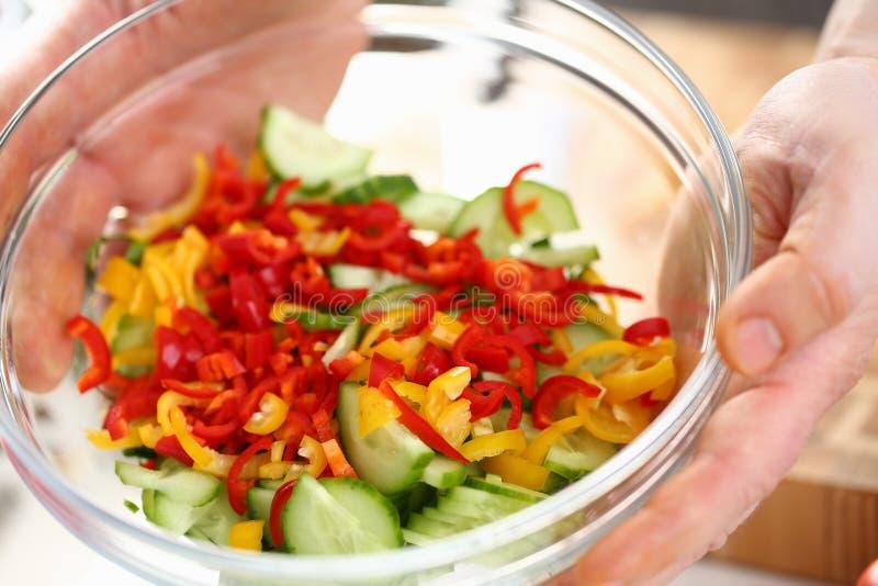Mains masculines tenant saladier végétal coupé images stock