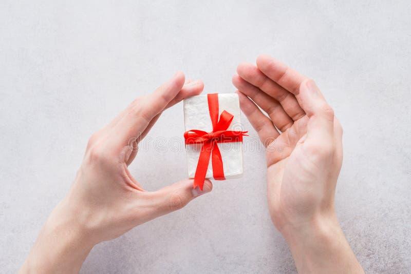 Mains masculines tenant un boîte-cadeau pour le jour de valentines image libre de droits
