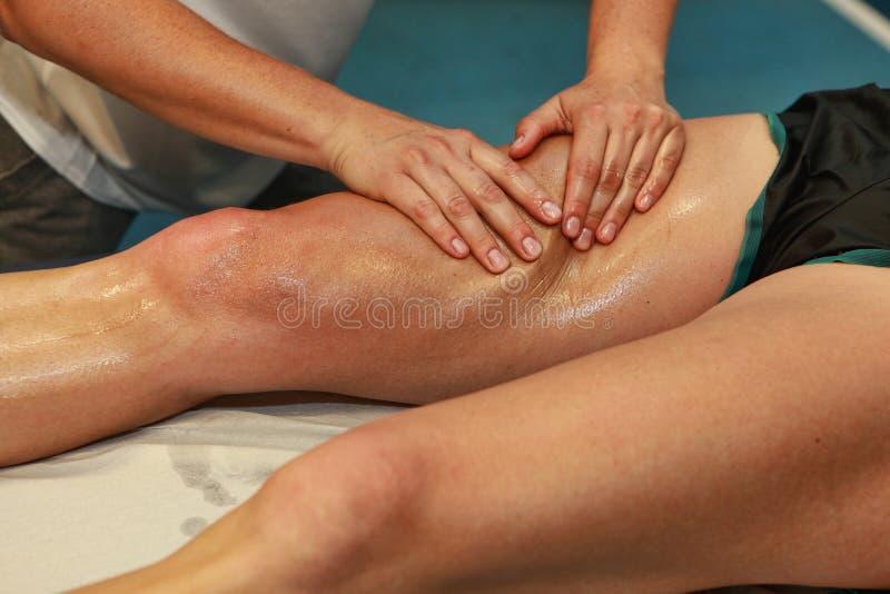 Mains massant la cuisse de l'athlète après fonctionnement images stock