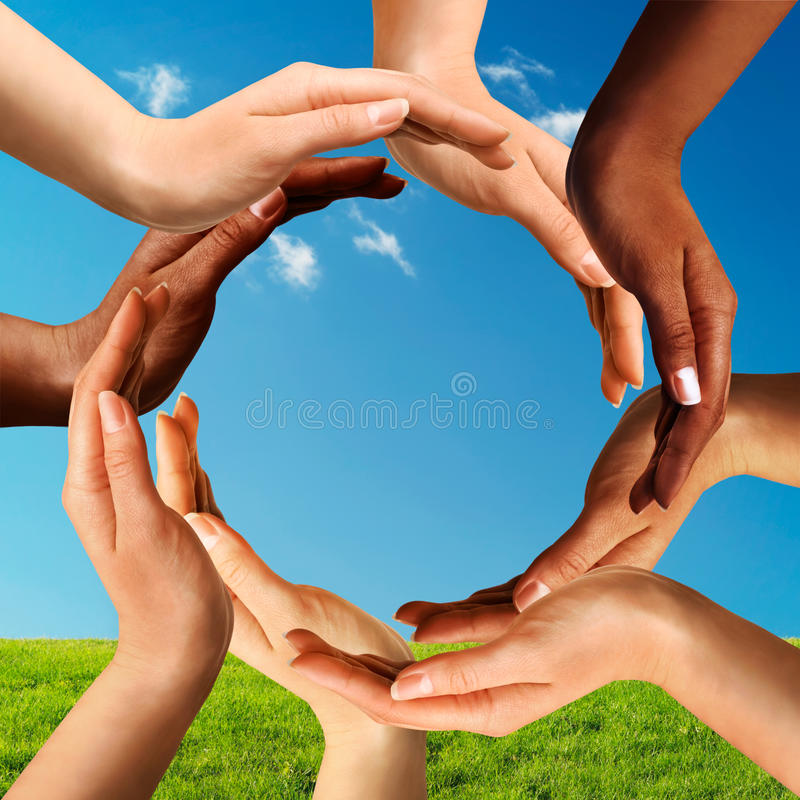 Mains multiraciales effectuant un cercle ensemble photo stock