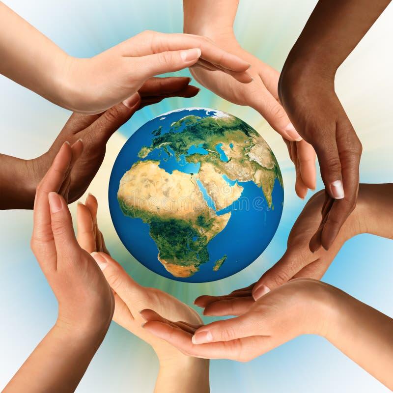 Mains multiraciales entourant le globe de la terre images stock