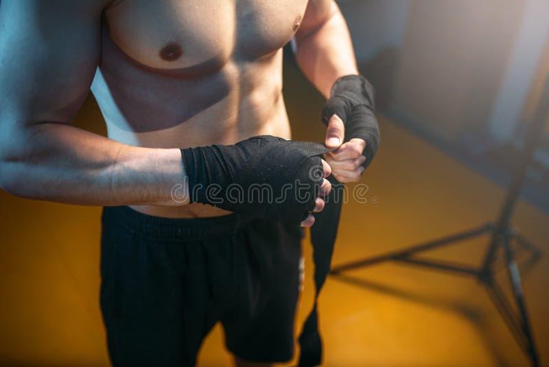 Mains musculaires de personne masculine dans des bandages noirs photo libre de droits