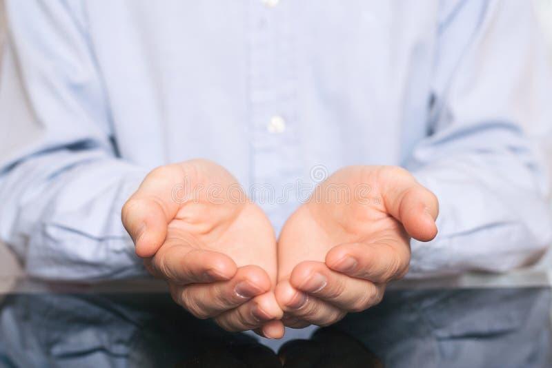 Mains ouvertes de signe de l'homme de prier homme dans la chemise jugeant quelque chose imaginaire sur des paumes de ses mains images libres de droits