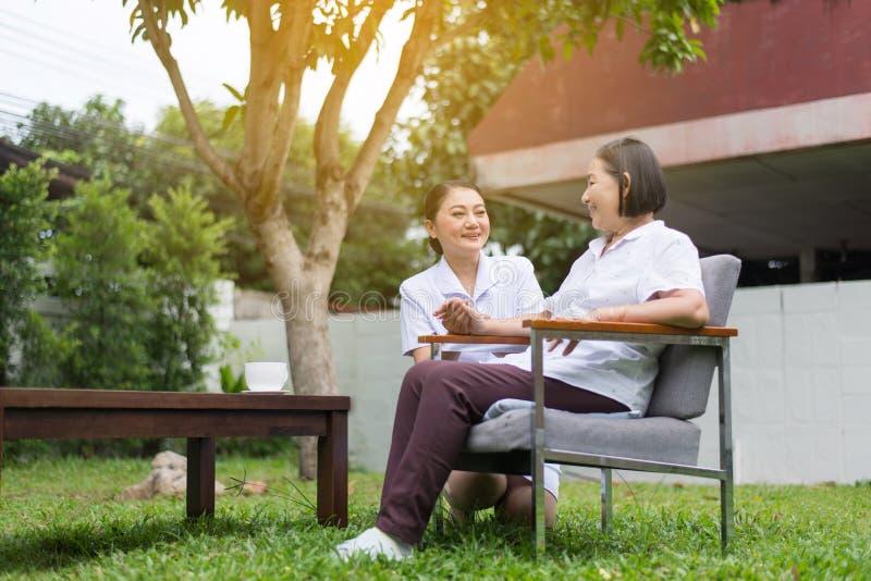 Mains patientes supérieures de femme se tenant avec le travailleur social, concept de soins en maison de retraite photos libres de droits