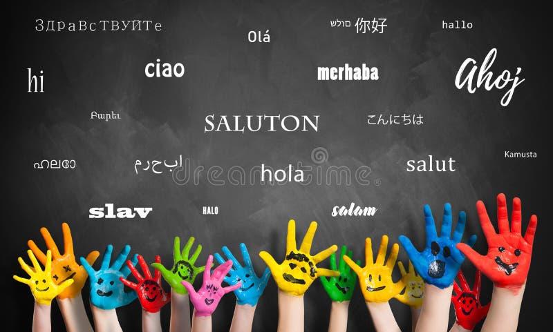"""Mains peintes d'enfants devant un tableau noir avec le mot """"bonjour """"dans beaucoup de langues photo stock"""