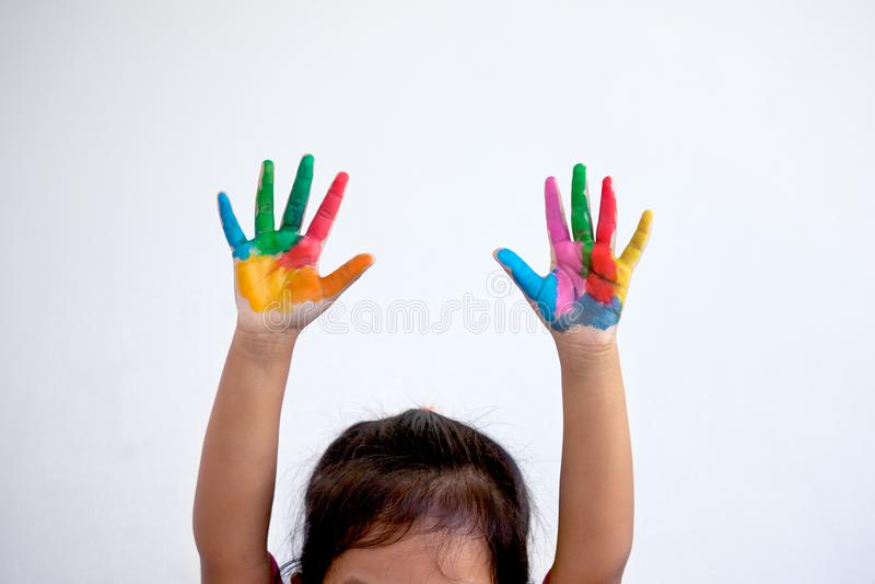 Mains peintes de la fille de petit enfant en peinture colorée image stock